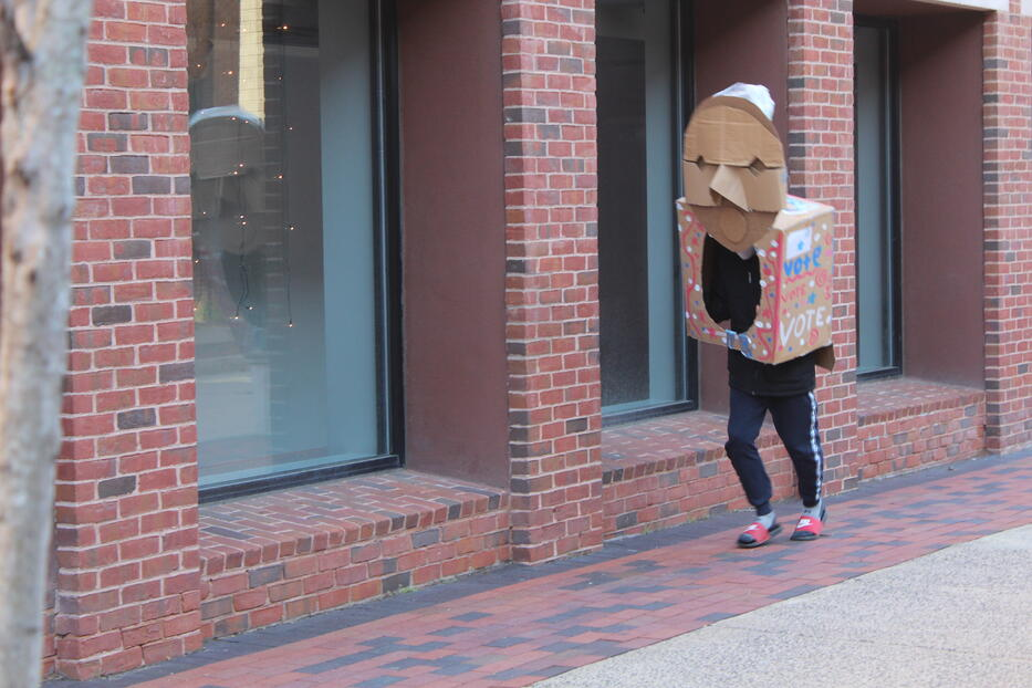 A student dressed as a ballot box marches down the street