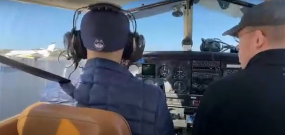 Two men sit in the cockpit of a plane. The man on the left is dressed in a blue hat and jacket. The man on the right is also dressed in a blue hat and sweater.