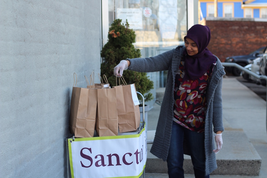 SumiyaKhan,KitchenProgram Manager at Sanctuary Kitchen, standing beside curbside pickups. Photo courtesy of Lucy Gellman.