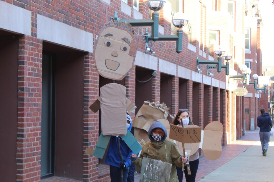Students marching with puppets and voter signs